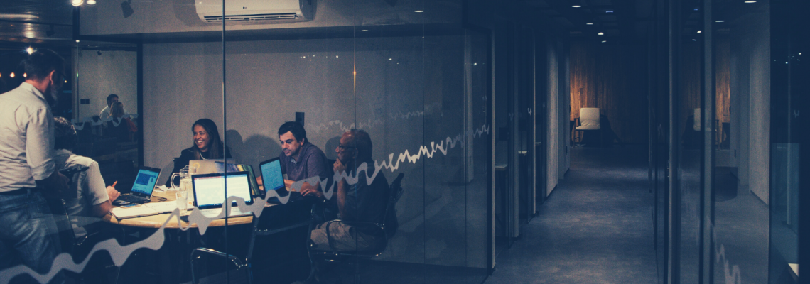 Startup employees sit around a table in a conference room at the end of a long hallway